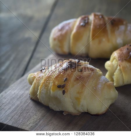 Mini croissants filled with cheese on wooden table