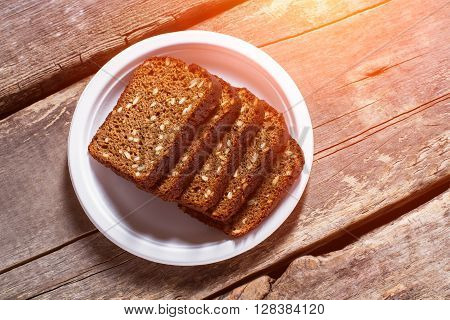 Sliced bread on a plate. Slices of brown grain bread. Recipe of homemade bread. Healthy savoury food.
