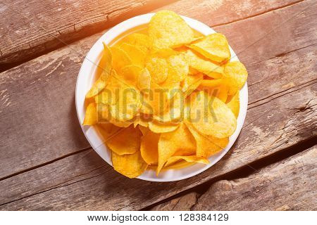 Potato chips pile on plate. Chips on brown wooden background. Fast snack at the diner. Example of processed food.