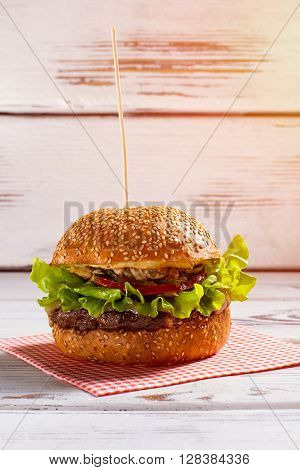 Burger on wooden stick. Big burger laying on napkin. White table with fresh beefburger. Fat and calories.