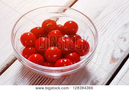Tomatoes in a glass bowl. Bowl with small ripe tomatoes. Vegetables on white wooden table.  Ingredient for a salad.