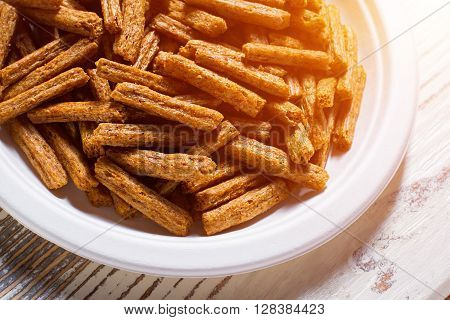 Pile of crackers on plate. White plate with bread crackers. Crispy sticks on white table. Simple snack recipe.