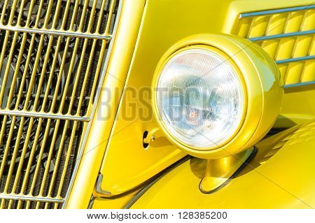 bright yellow vintage vehicle grille and headlight closeup