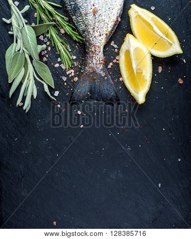 Tail of fresh raw Dorado or sea bream fish on black slate stone board with spices, herbs, lemon and salt. Top view, copy space, vertical