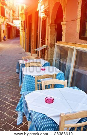 Empty tables of street cafes at sunny noon in the tourist area of the city, Chania, Crete, Greece