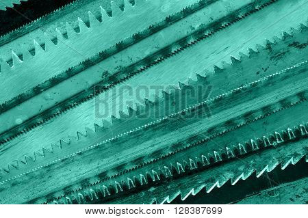 Closeup various hacksaw blades pattern. Toned green.