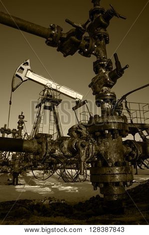 Valve pipe and oil pump. Oilfield petroleum industrial site. Toned sepia.