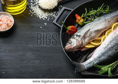 Raw uncooked seabass fish with herbs, spices and rice in cast iron cooking pan on black wooden background. Copy space, selective focus