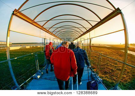 people with backpacks and luggage go through a covered walkway to the plane low cost flights,  outdoors, airport