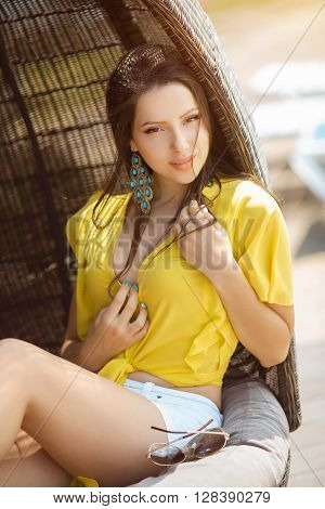 Portrait of beautiful young woman in yellow t-shirt and white shorts relaxing on chaise lounge near swimming pool