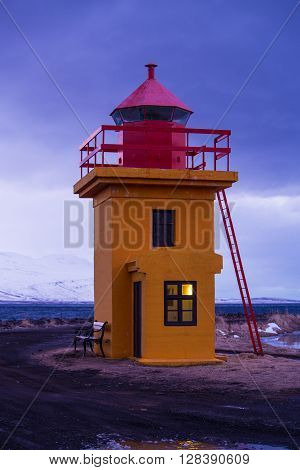 Orange lighthouse at the Ocean in the evening Iceland