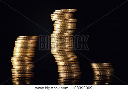 Stacks of coins isolated on black background, financial graph concept