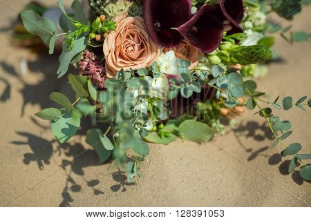Bride's Pink Orange and White Wedding Bouquet Laying on Sand