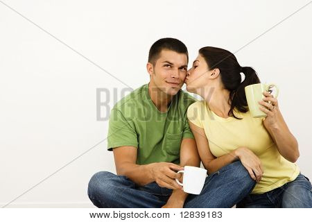 Couple sitting on floor drinking coffee with woman leaning over kissing man on cheek.