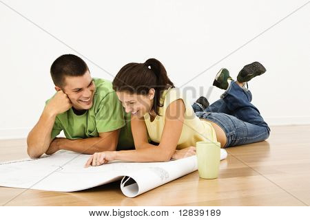 Attractive young adult couple lying on home floor with coffee cups smiling and looking at blueprints.