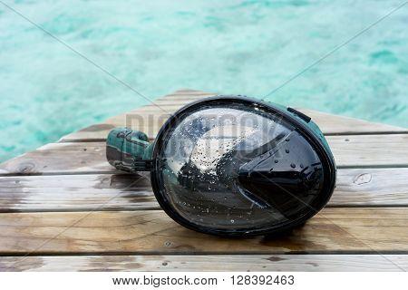 Black Snorkeling Mask on Dock at sea Maldives