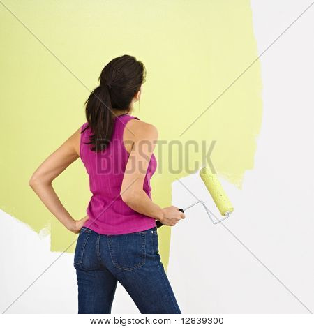 Woman standing and looking at partially painted wall holding paint roller.