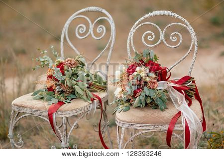 Beautiful wedding colorful bouquets for bride on retro chairs in forest. Beauty of colored flowers. Bridal accessories. Female decoration for girl. Details for marriage and for married couple