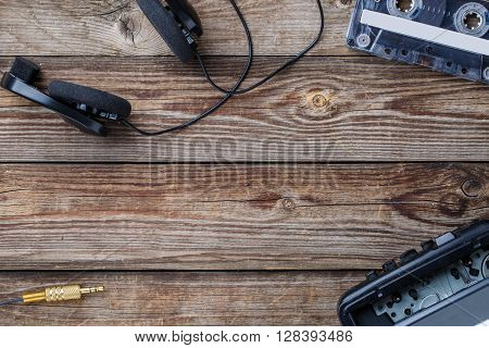 Frame of cassette tape, cassette player and headphones over wooden table. top view. Retro concept with empty space for text, logo, etc.