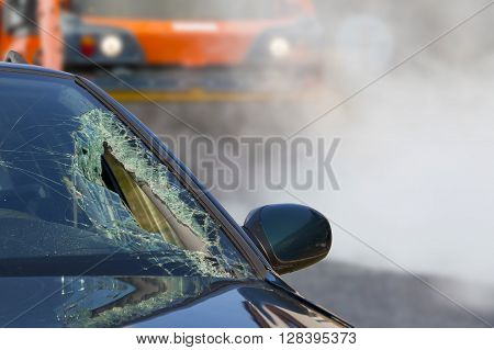 Broken glass of car in an accident and road roller