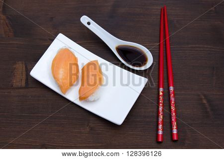 Nigiri with salmon on a wooden table seen from above
