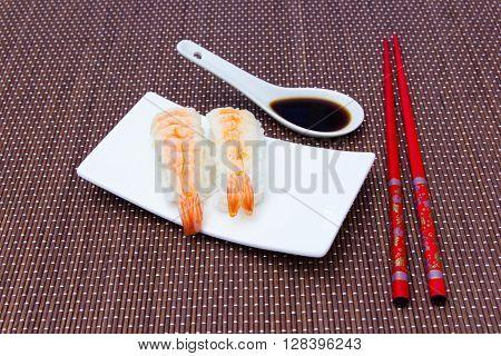 Nigiri with shrimp on a bamboo mat