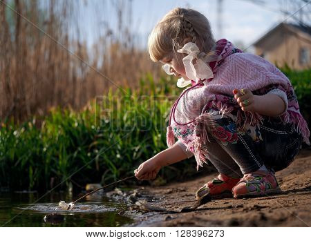 Small child plays on the bank near the water. Girl playing wooden branch in the water sitting on the shore of squatting. Little girl. Summer, green grass. Against the backdrop of a village house