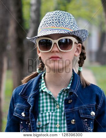 Girl teenager with glasses and hat, in the city. Park, green trees. Denim jacket, two pigtails