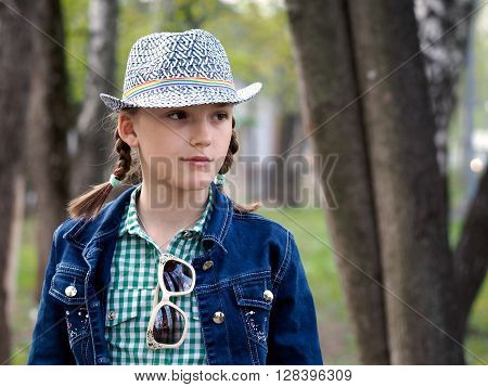 Teen girl in a hat in the city. Park, green trees. Denim jacket, two pigtails