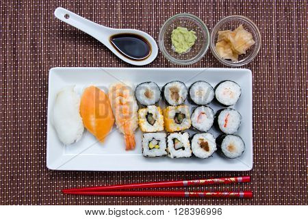 Tray of sushi on a placemat bamboo seen from above