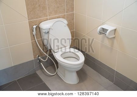 White toilet bowl in a public bathroom.