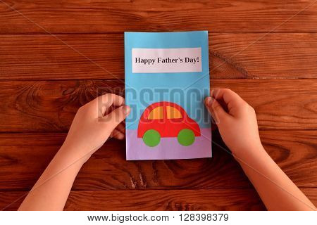 Child holding a father's day card. Greeting card father's day. How to make a greeting card father's day