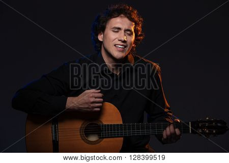 Man playing on guitar over dark background