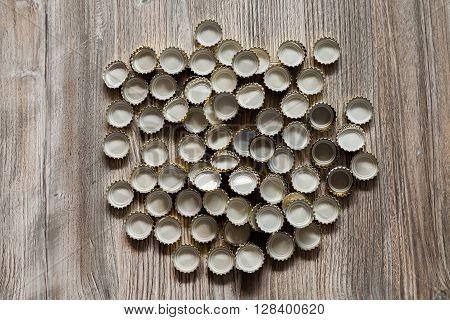 alot of bottle caps lies on wood texture