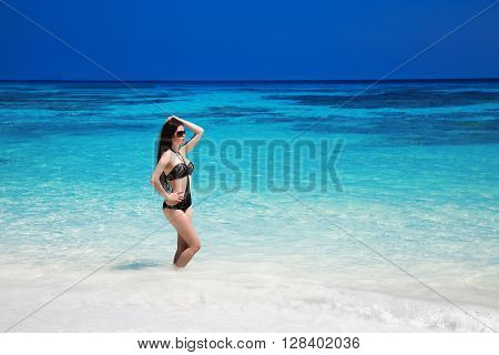 Elegant Sexy Woman In Black Bikini On Tropical Beach, Exotic Island. Beautiful Slim Brunette Sun-tan