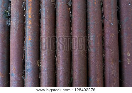 Old, rusty, dirty pipes are piled upright
