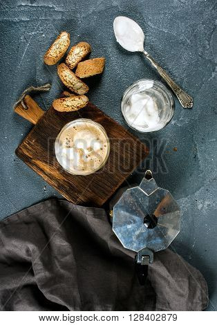 Glasses of coffee with ice cream on rustic wooden board, steel Italian Moka pot over grey concrete textured background, top view, vertical