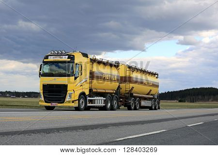 JOKIOINEN, FINLAND - APRIL, 30 2016: Yellow Volvo FH tank truck for bulk transport on the road on a cloudy day.