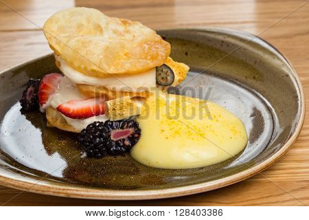 millefeuille with orange foam on a wooden table