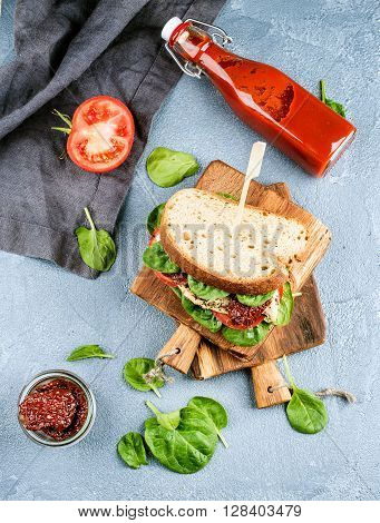 Chicken, sun-dried tomato and spinach sandwich with spicy sauce on small rustic wooden board over grey concrete textured background, top view, vertical
