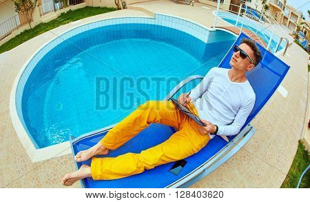 young man relaxing on the chaise-longue near the pool