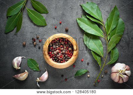 Herbs and spices selection. Bay leaves, pepper and garlic on slate background.