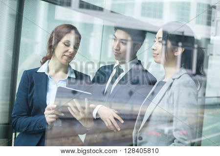 Group of business people discuss on tablet pc