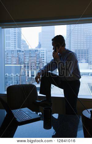 Meia-idade macho caucasiano no gabinete no telefone com horizonte em segundo plano.
