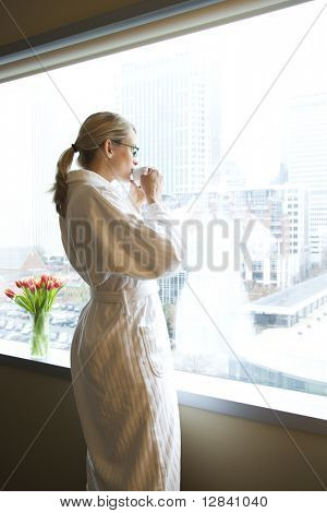 Mid-adult Caucasian woman with coffee cup looking out window.