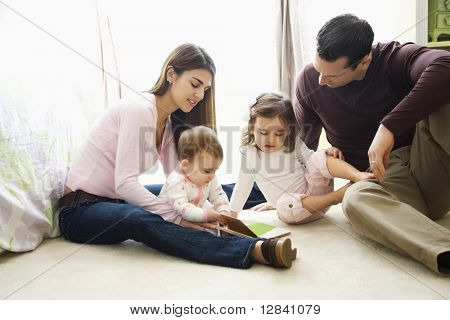 Caucasian girl children with mother and father sitting on bedroom floor looking at book.
