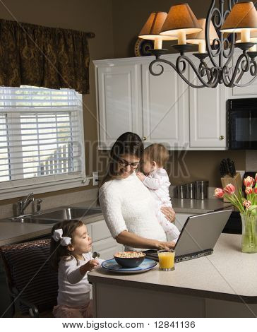 Caucasian mother holding baby  and typing on laptop computer with girl eating breakfast in kitchen.