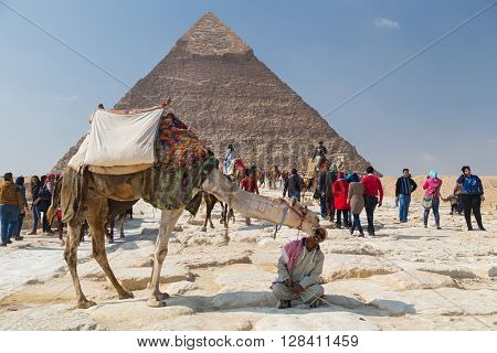 CAIRO, EGYPT - FEBRUARY 3, 2016: Local man renting camel to tourist in front of the Great Pyramid of Giza.