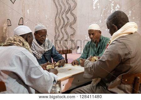 ASWAN, EGYPT - FEBRUARY 5, 2016: Local elderly men playing dominos on Nubian village street.