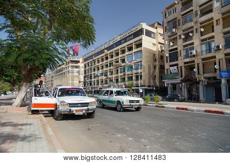 ASWAN, EGYPT - FEBRUARY 5, 2016: Local man entering old Peugeot 504 taxi at street.